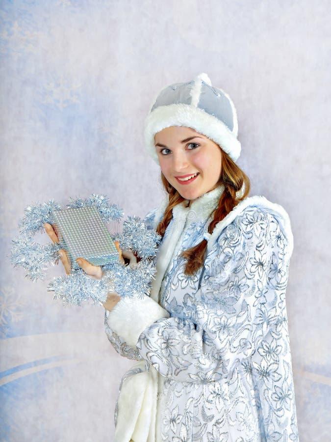 A menina de sorriso vestiu-se no traje tradicional do Natal do russo da donzela da neve de Snegurochka com caixa atual, imagem de stock