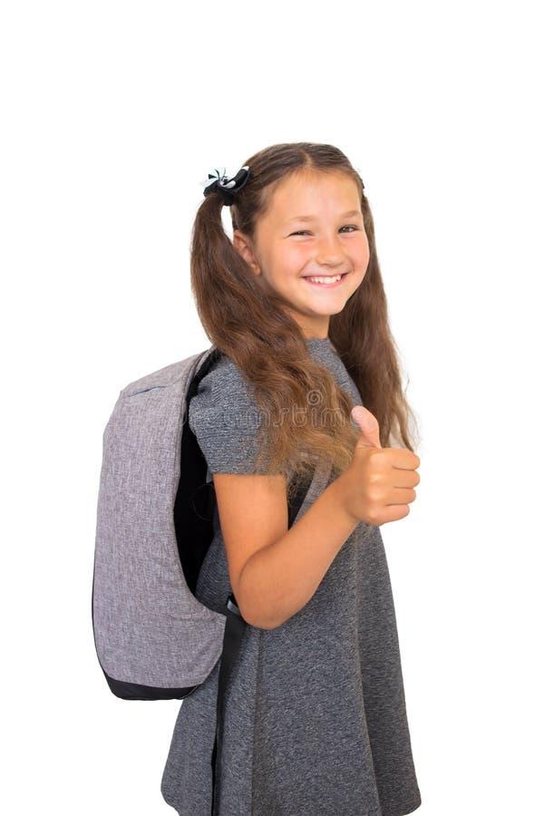 A menina de sorriso vestiu-se nos polegares das mostras da farda da escola acima do sinal foto de stock royalty free