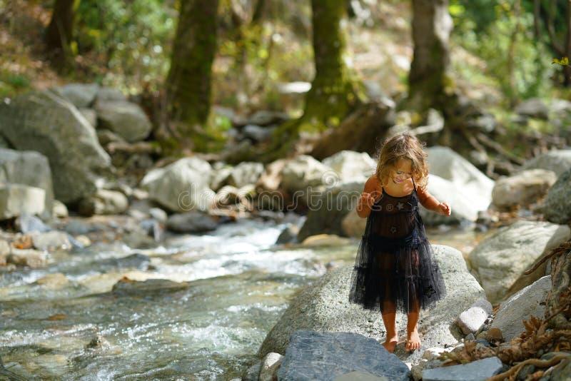 menina de três anos brincando com uma velha boneca perto de um rio na linda natureza da montanha Dirfi em Eubeoa fotos de stock royalty free