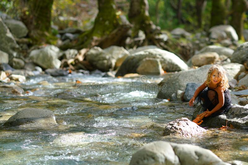 menina de três anos brincando com uma velha boneca perto de um rio na linda natureza da montanha Dirfi em Eubeoa fotos de stock