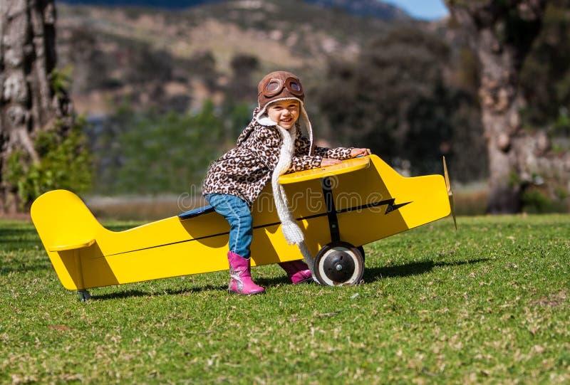 Menina de três anos no avião amarelo do brinquedo fora fotografia de stock