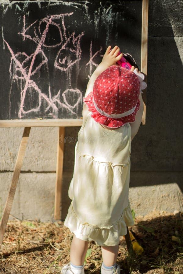 Menina de um ano em um chapéu vermelho fotografia de stock royalty free