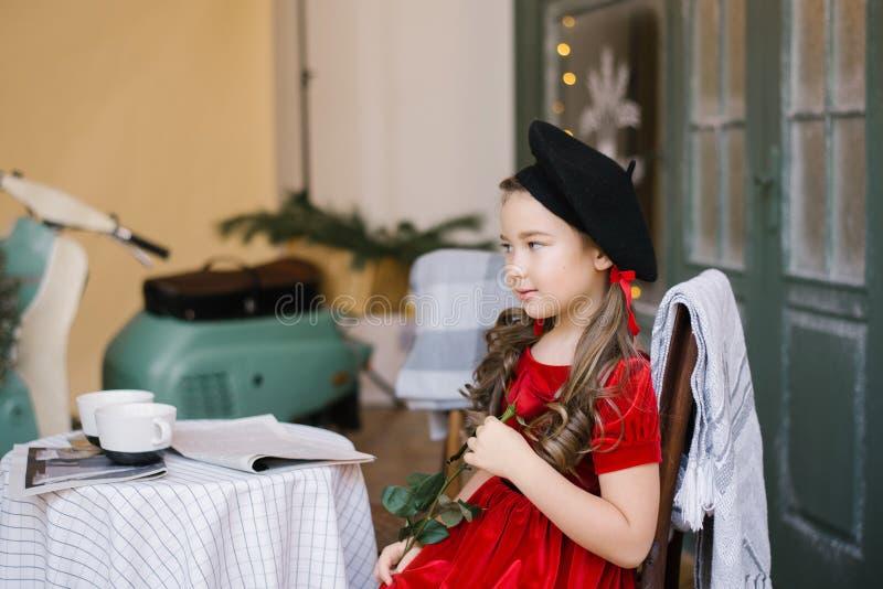 Menina de um vestido vermelho de veludo e uma boina preta sentada em uma mesa de café imagens de stock royalty free