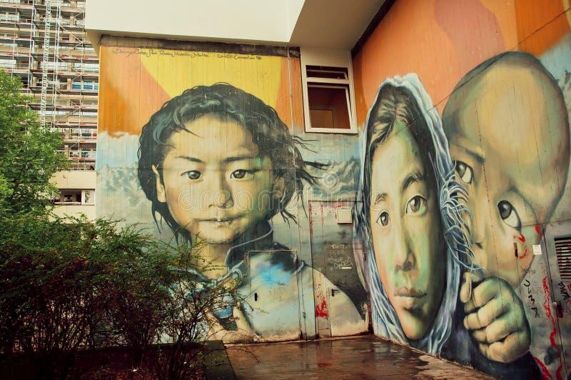 Menina de uma família de refugiado na parede com arte da rua fotografia de stock royalty free