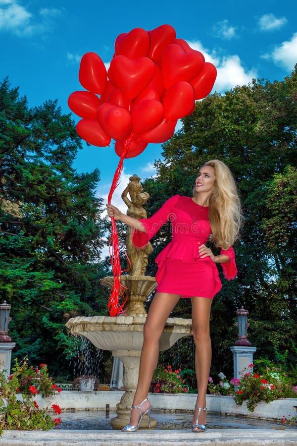 A menina de Valentine Beautiful com balões vermelhos ri, no parque Mulher nova feliz bonita Festa de anos Modelo alegre que levan imagens de stock