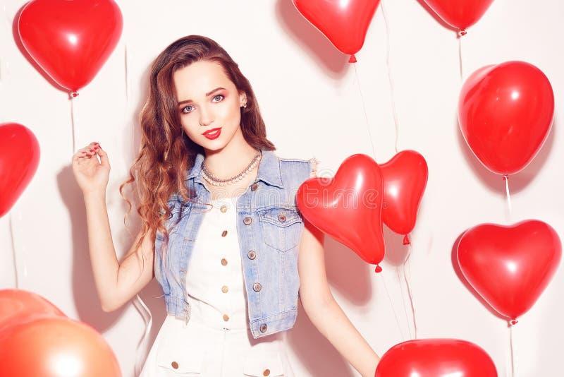 Menina de Valentine Beauty com os balões de ar vermelhos que ri, no fundo branco Mulher nova feliz bonita O dia da mulher Festa n imagens de stock royalty free