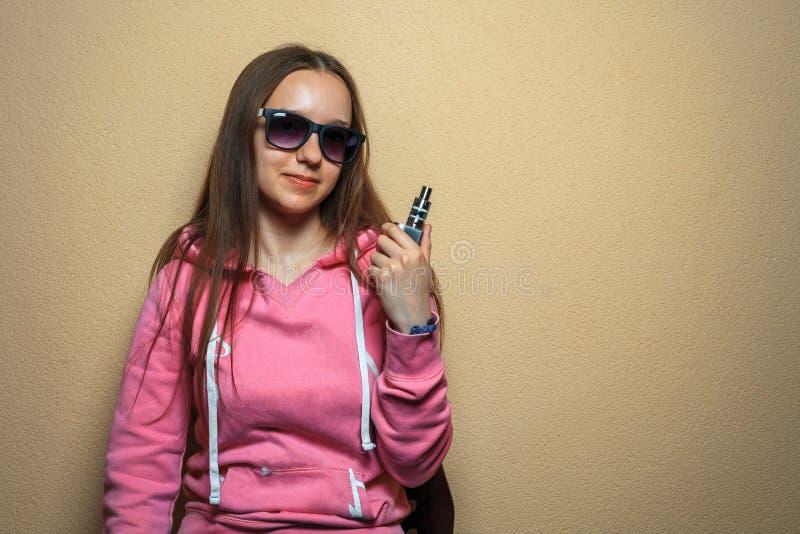 Menina de Vape Retrato da mulher bonito nova no hoodie cor-de-rosa e nos óculos de sol que guardam um cigarro eletrônico em sua m fotografia de stock royalty free