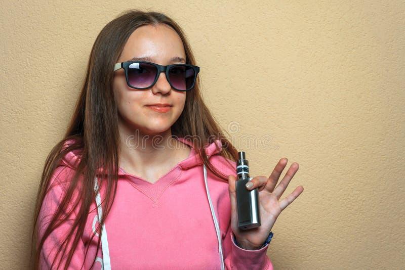 Menina de Vape Retrato da mulher bonito nova no hoodie cor-de-rosa e nos óculos de sol que guardam um cigarro eletrônico em sua m imagens de stock