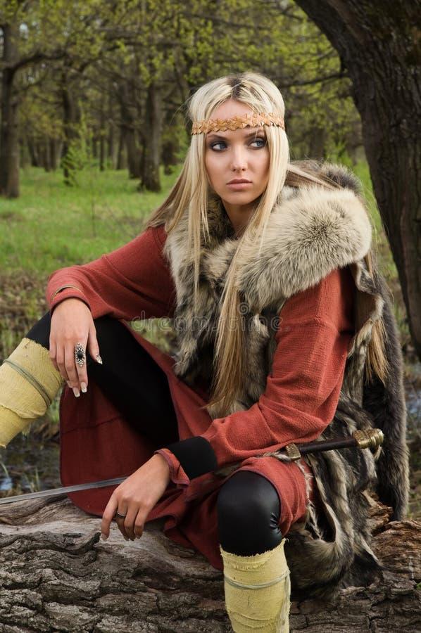 Menina de Viquingue com espada em uma madeira imagem de stock