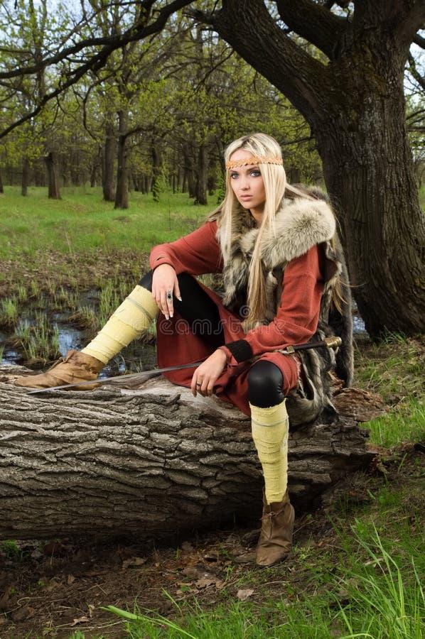 Menina de Viquingue com espada em uma madeira imagem de stock royalty free
