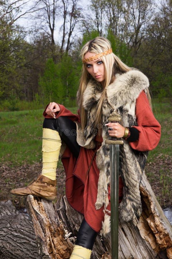 Menina de Viquingue com espada em uma madeira imagens de stock