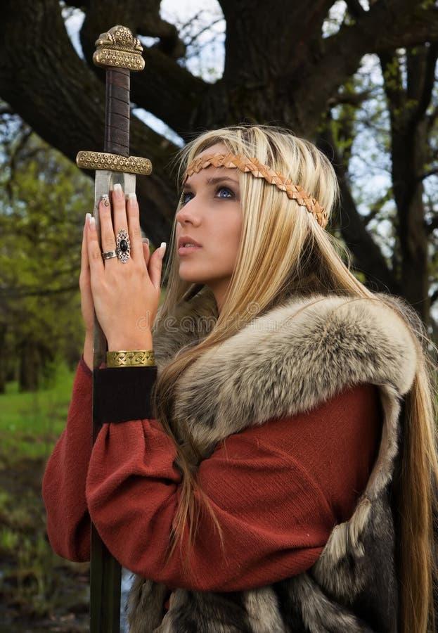 Menina de Viquingue com espada em uma madeira fotografia de stock royalty free