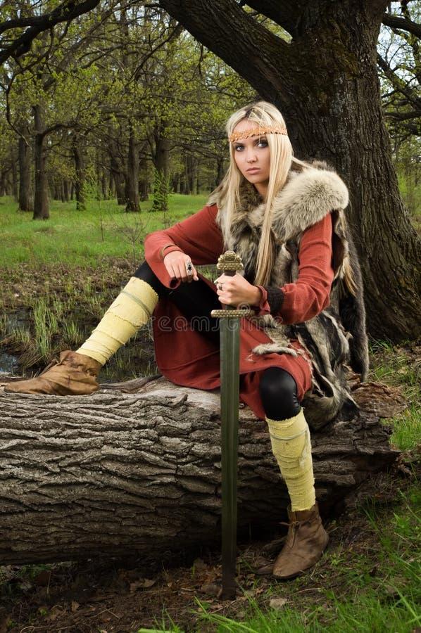Menina de Viquingue com espada em uma madeira fotos de stock royalty free