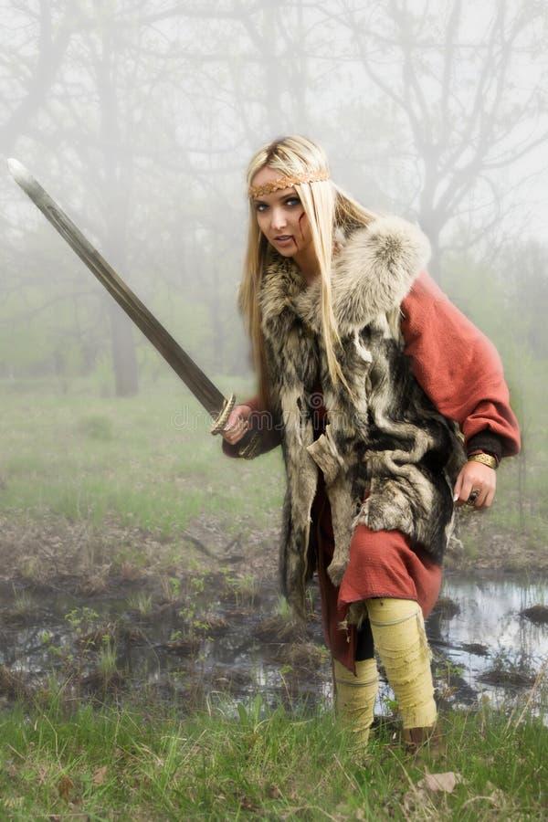 Menina de Viquingue com espada em uma madeira da névoa fotografia de stock royalty free