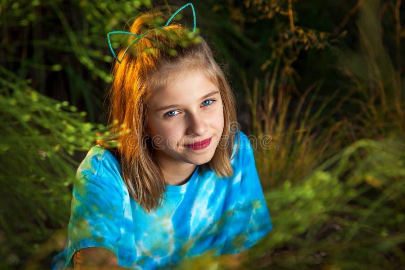 Menina de vista Sassy que Smirking na câmera atrás dos ramos de árvore foto de stock