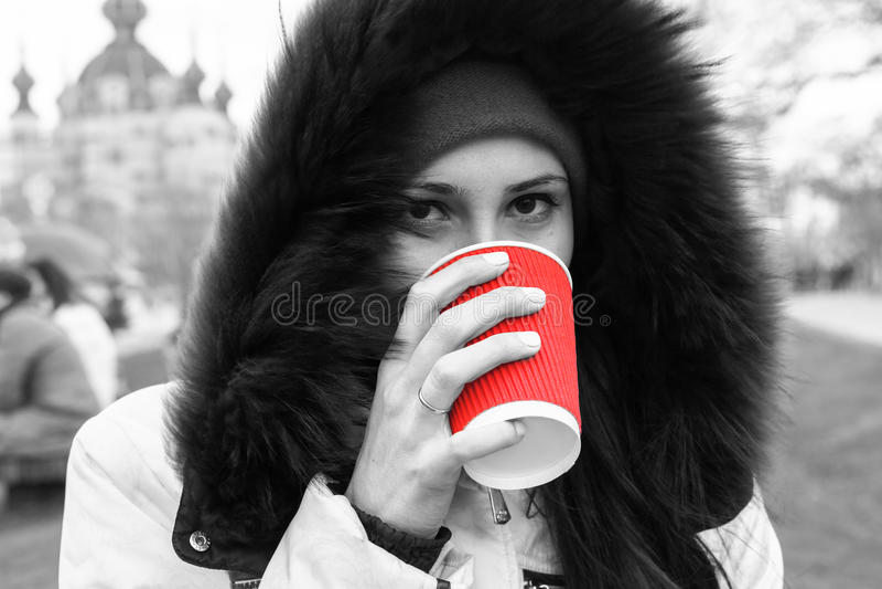A menina de Yound bebe um copo vermelho do chá quente preto e branco fotografia de stock royalty free