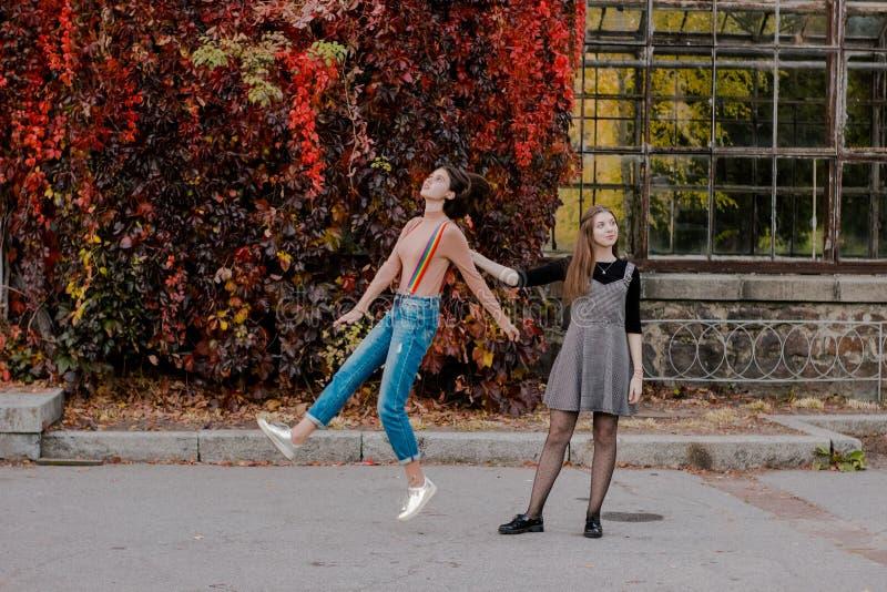 A menina decola ser ao lado da jovem mulher que a mant?m andar no parque do outono imagem de stock