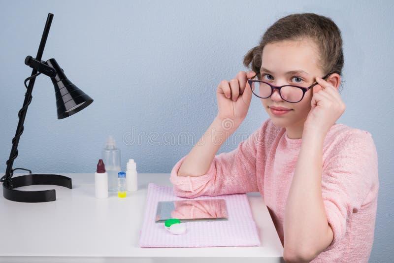 A menina decola seus vidros, sentando-se na tabela, a fim vestir a lente para corrigir a vista imagens de stock