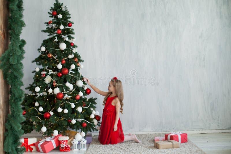 A menina decora presentes de uma casa de férias do ano novo de árvore de Natal foto de stock