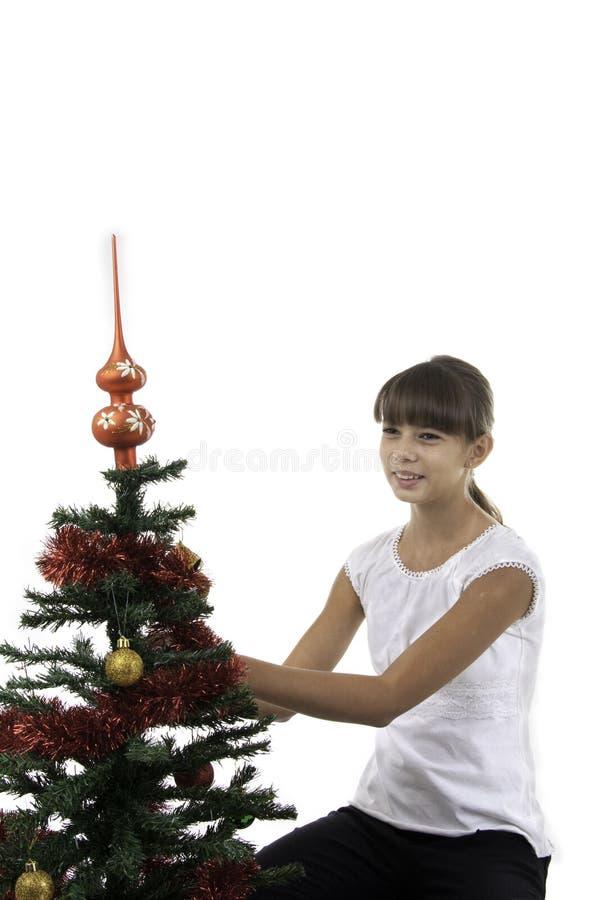 A menina decora uma árvore do ano novo