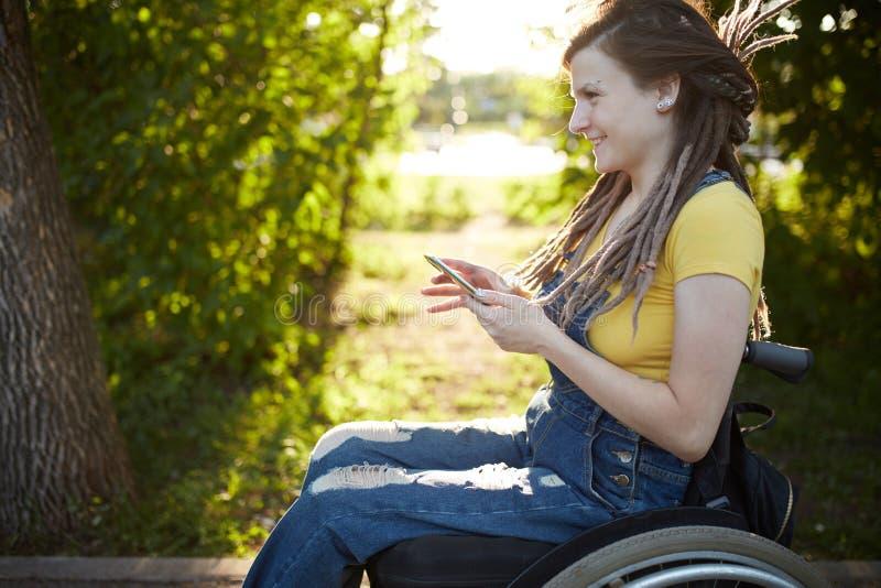 Menina deficiente de sorriso que tem o divertimento com seu telefone esperto imagens de stock royalty free