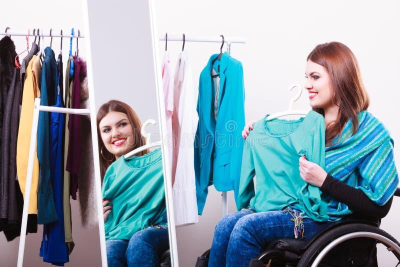 Menina deficiente na cadeira de rodas que escolhe a roupa fotografia de stock royalty free