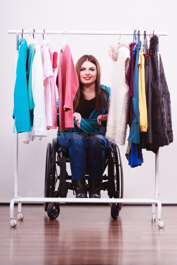 Menina deficiente na cadeira de rodas que escolhe a roupa imagens de stock