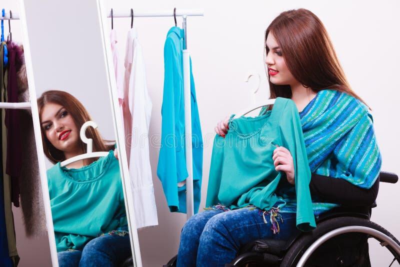 Menina deficiente na cadeira de rodas que escolhe a roupa foto de stock