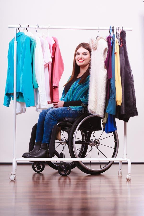 Menina deficiente na cadeira de rodas que escolhe a roupa fotos de stock royalty free