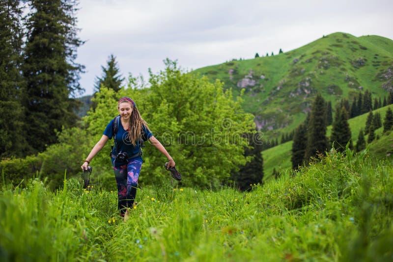 A menina deleitada anda com os pés descalços na grama Moça com dreadlocks que anda na floresta fotos de stock