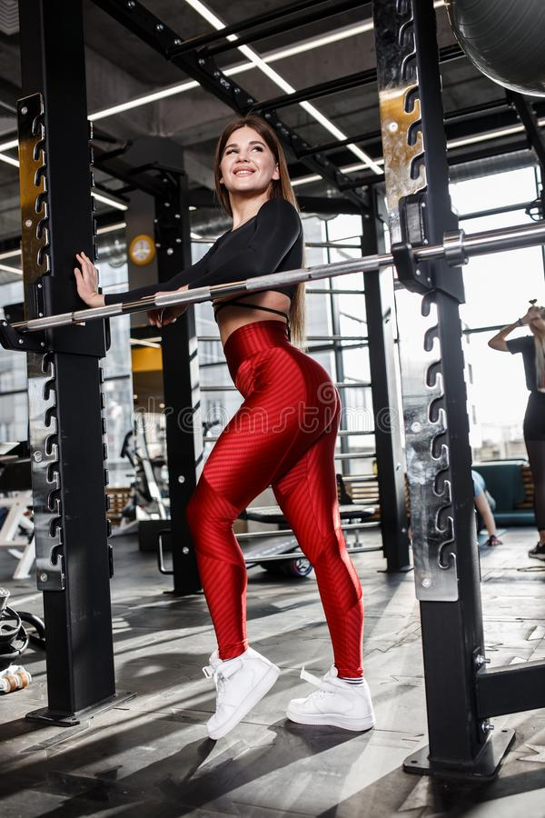 A menina delgada bonita na roupa brilhante ? moda dos esportes faz poses ao lado da barra horizontal no gym moderno fotografia de stock