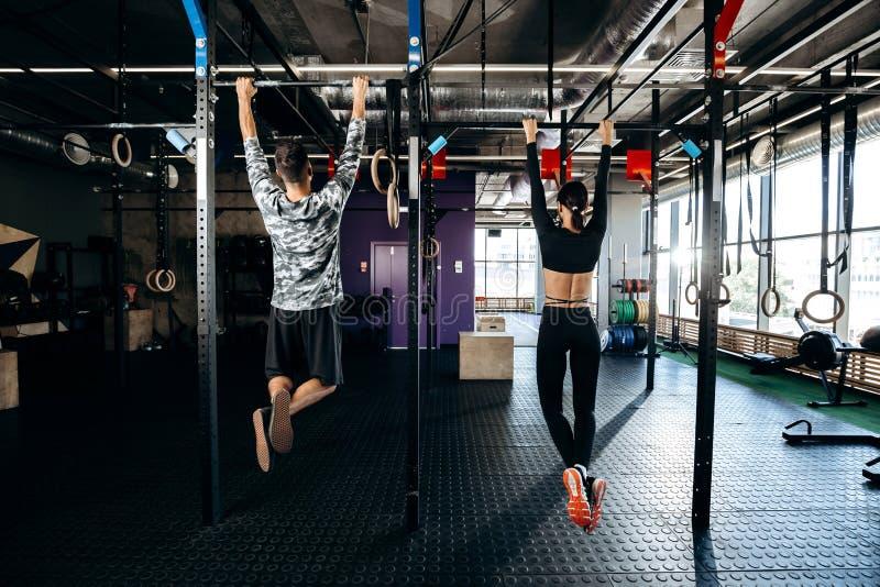 A menina delgada e o homem atlético vestidos na roupa dos esportes estão levantando na barra no gym fotos de stock royalty free