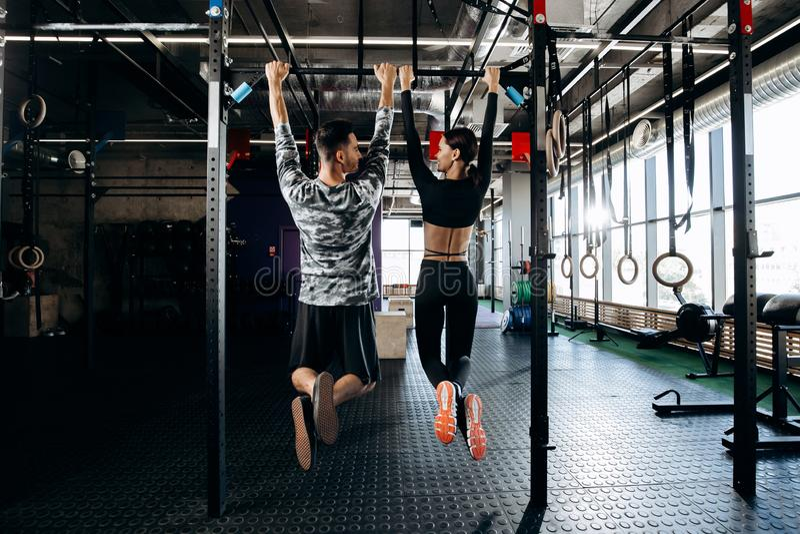 A menina delgada e o homem atlético vestidos na roupa dos esportes estão levantando na barra no gym imagem de stock