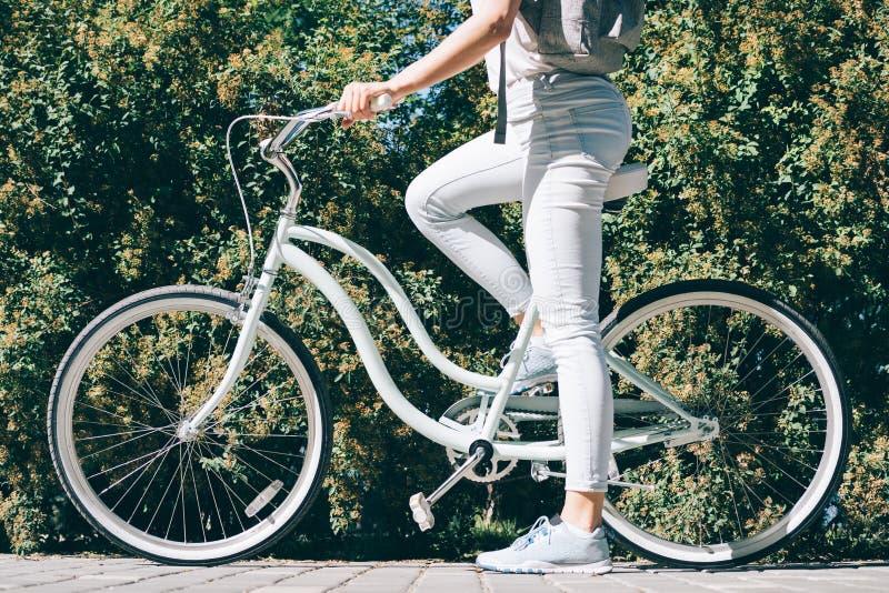 A menina delgada em calças de brim e em sapatilhas de um t-shirt do branco senta-se em seu s fotografia de stock