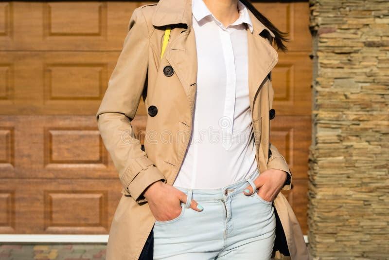 Menina delgada em um revestimento bege, em uma calças de ganga e em uma camisa branca exteriores fotografia de stock royalty free