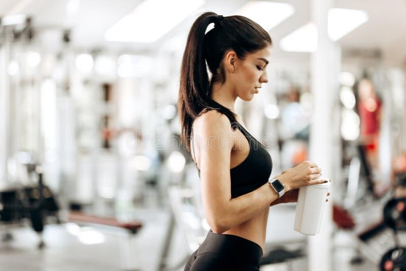A menina delgada está mantendo uma garrafa com água em sua mão no gym fotos de stock royalty free