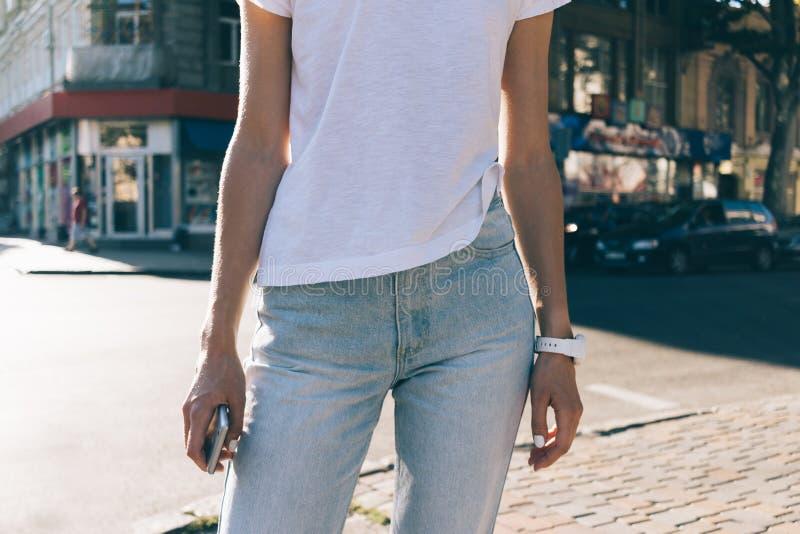Menina delgada nas calças de brim e em um t-shirt branco no fundo de t imagem de stock royalty free