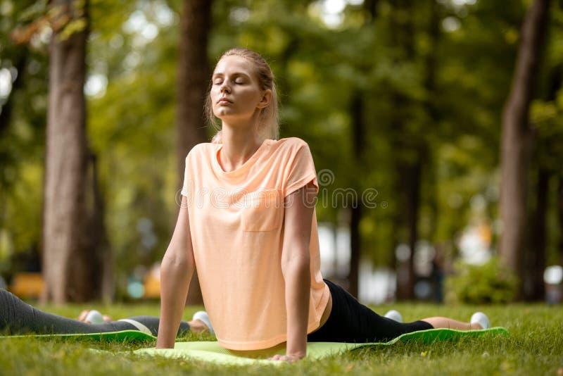 Menina delgada nova com os olhos de fechamento que fazem exerc?cios da ioga na esteira da ioga na grama verde no parque em um dia imagens de stock royalty free