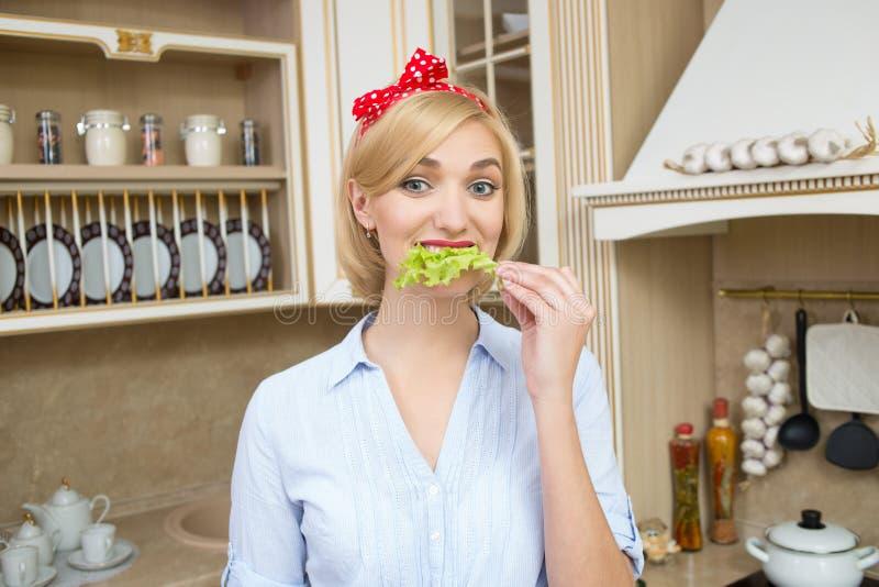 Menina delgada que come as folhas da alface imagens de stock royalty free
