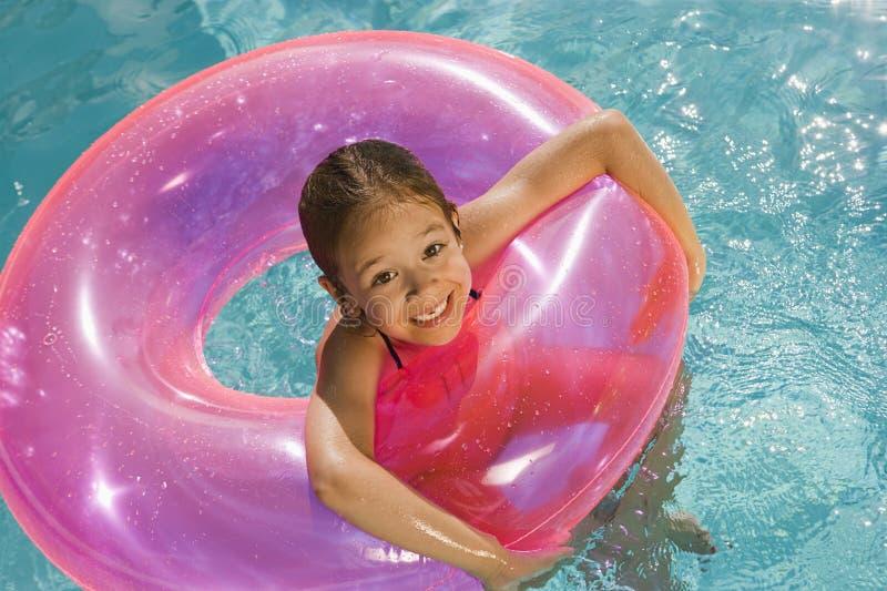 Menina dentro do tubo cor-de-rosa do flutuador na associação fotografia de stock royalty free