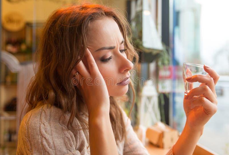 Menina deprimida que obtém bebida apenas em uma barra imagem de stock