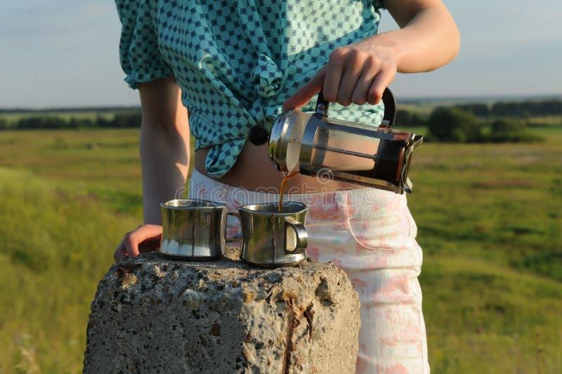 A menina derrama o café em dois copos de uma francês-imprensa no ar livre Paisagem do VERÃO imagens de stock