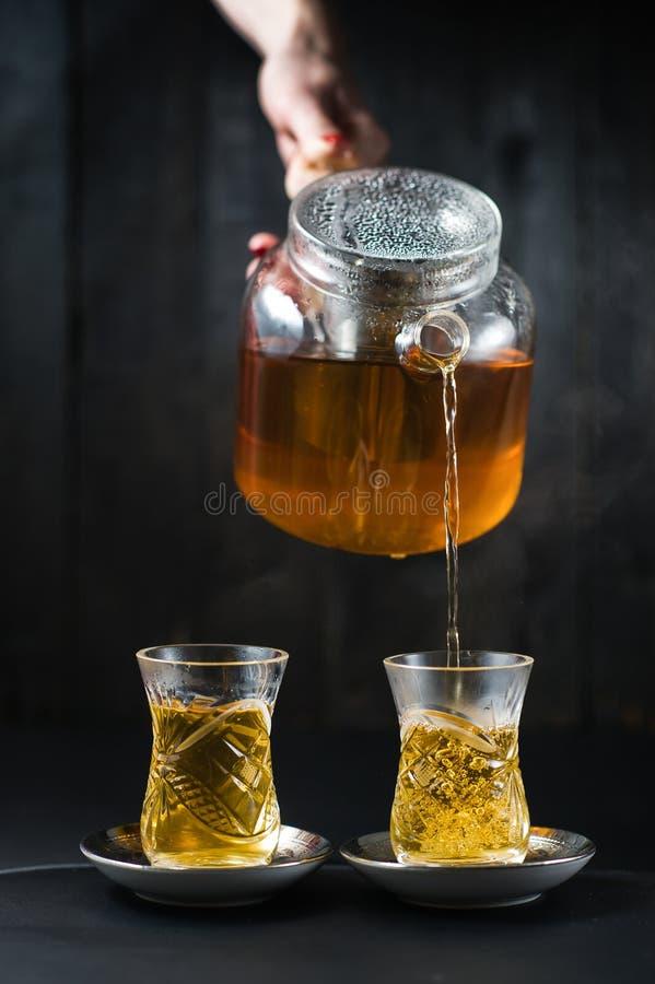 A menina derrama o chá em um armud foto de stock