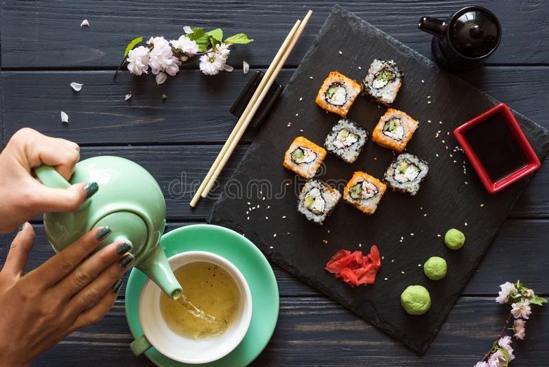 A menina derrama o chá em um copo com um bule perto do sushi imagem de stock royalty free
