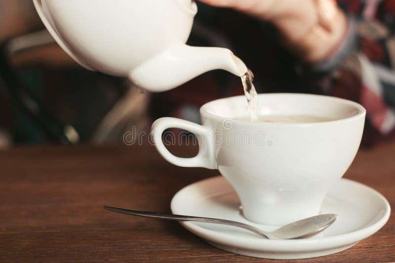 A menina derrama um copo do chá fotografia de stock royalty free