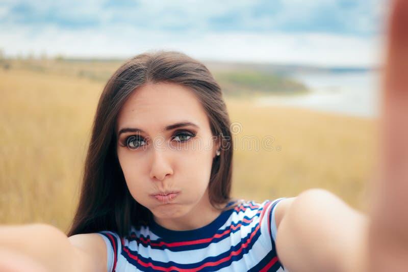 Menina desajeitada que tenta tomar um Selfie na natureza fotografia de stock royalty free