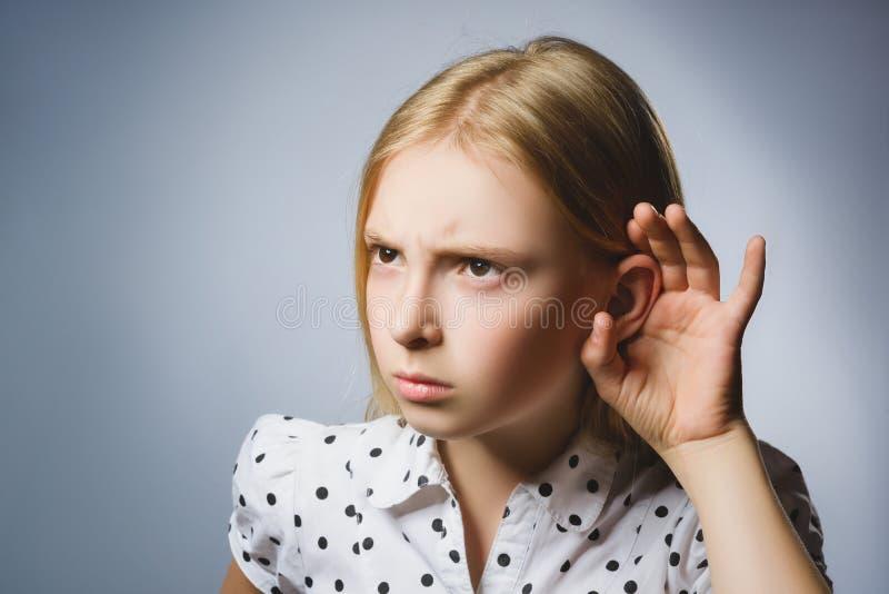 A menina desapontado curiosa escuta A audição da criança do retrato do close up algo, pais fala, mão ao gesto da orelha isolada imagem de stock