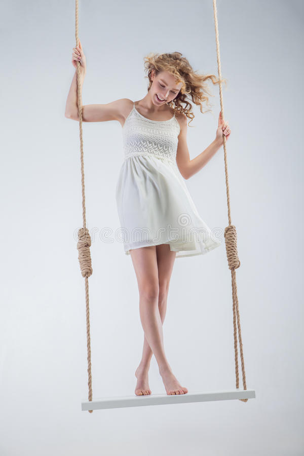 Menina descalça dos jovens no balanço que olha para baixo foto de stock