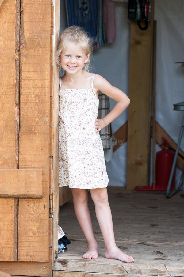 Menina descalça em suportes dos sundress de um verão na entrada da vertente fotos de stock royalty free