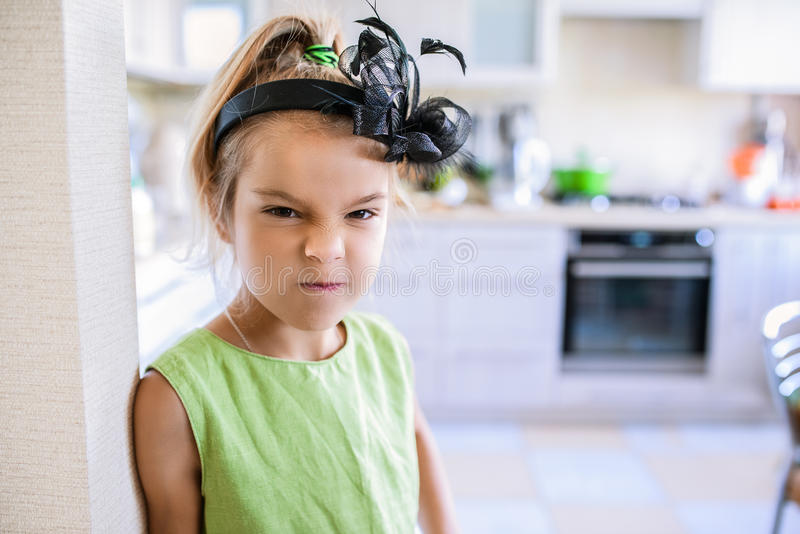 Menina descontentada bonita pequena no vestido verde foto de stock